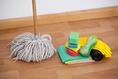 Mop and cleaning equipment on wooden floor against wall