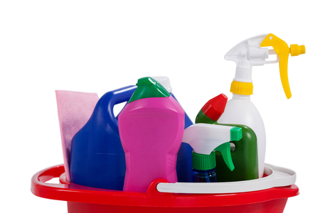 Various household cleaning supplies in a bucket on white background