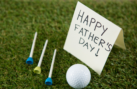 Close up of greeting card with happy fathers day text by golf ball and tees on grassy field Stock Photo