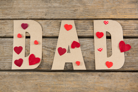 Overhead view of dad text decorated with heart shape on wooden table Banco de Imagens