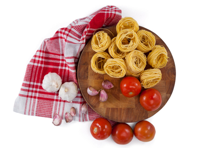 Raw fettuccine with tomatoes, garlic, onions and napkin cloth against white background Stock Photo