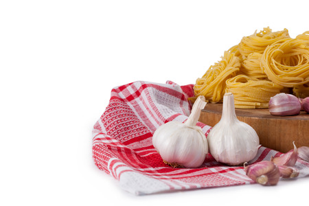 Raw fettuccine with garlic, onions and napkin cloth against white background Stock Photo