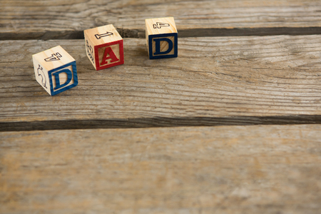 High angle view of cube shapes with dad text and numbers on wooden table Banco de Imagens