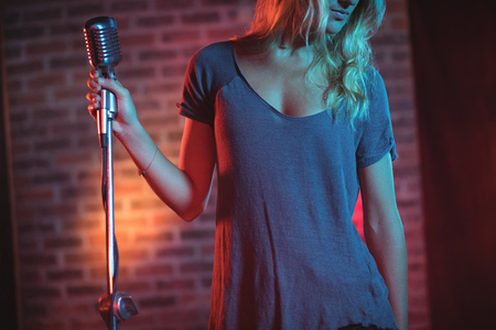 symphonic: Mid section of female singer with microphone standing in nightclub Stock Photo