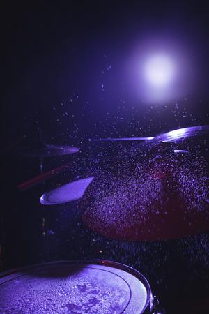 Water splashing on drum set in illuminated nightclub Stock Photo