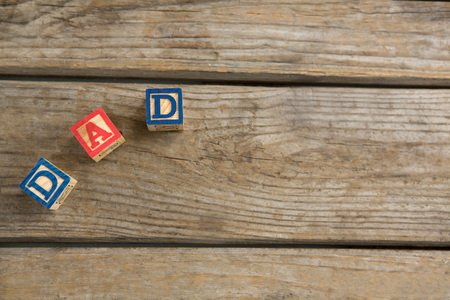 Overhead view of cube shapes with text dad on wooden table