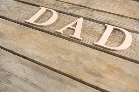 High angle view of beige dad text on wooden table