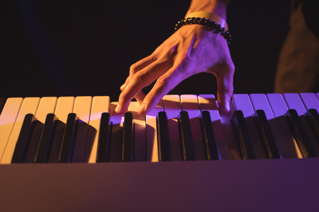 symphonic: Cropped hand of male musician playing piano in nightclub