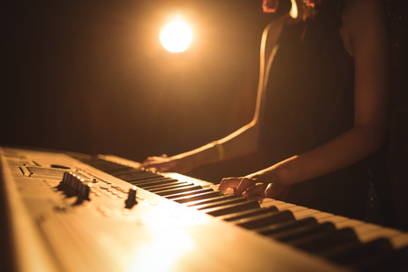 Mid section of female musician playing piano in illuminated music festival