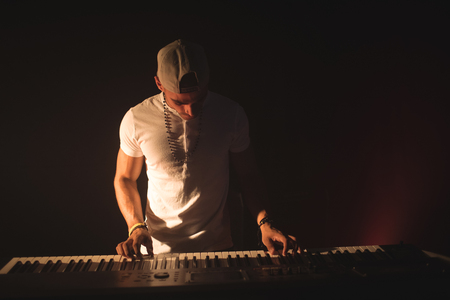 Confident male musician playing piano in nightclub