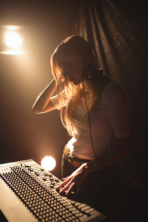 Confident female DJ playing music in illuminated nightclub