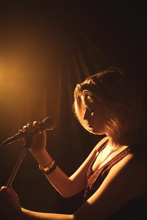 Confident female singer performing at music concert