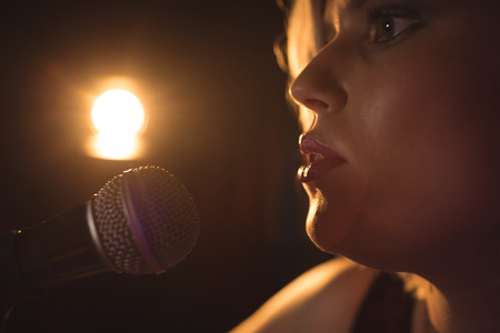 acoustics: Close up of female singer performing in music concert Stock Photo