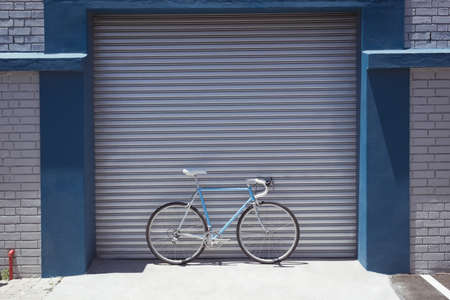 meta: Vintage bicycle parked by closed workshop during sunny day LANG_EVOIMAGES