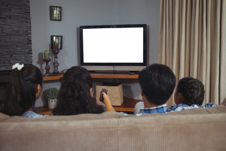 Family watching television together in living room at home 版權商用圖片 - 79751951