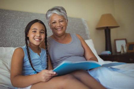 photo album: Portrait of grandmother and granddaughter holding photo album in bed room at home
