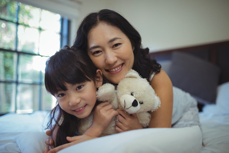 Portrait of mother and daughter relaxing on bed in bed room at home Stock Photo