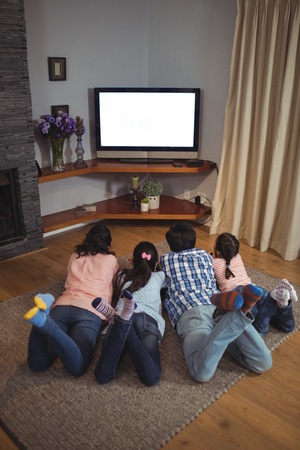 Family watching television together in living room at home Foto de archivo