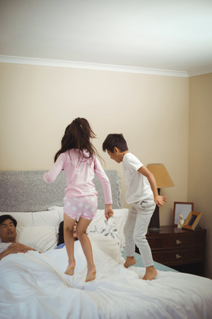 Siblings jumping on bed in bedroom at home Stock Photo