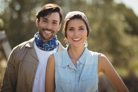 Portrait of happy young couple on sunny day at olive farm Stock Photo