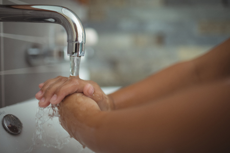 Close-up of girl washing hands in bathroom sink at home