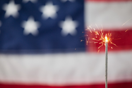 Close-up of sparklers burning against American flag background Stock Photo