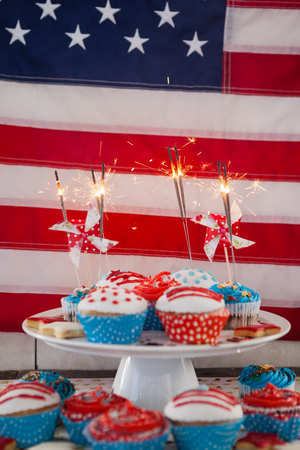 Burning sparkler on decorated cupcakes against American flag Stock Photo