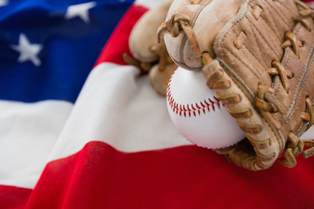 Close-up of baseball and gloves on an American flag Stock Photo
