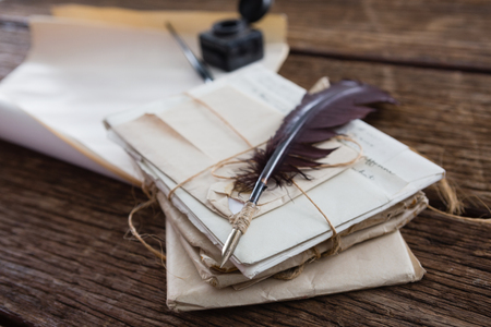 ink pot: Quill feather with legal documents arranged on wooden table