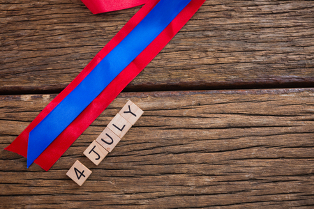 Date blocks with red and blue ribbon on wooden table Stock Photo