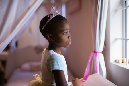 dressing up costume: Side view of thoughtful girl wearing crown standing in bedroom at home Stock Photo