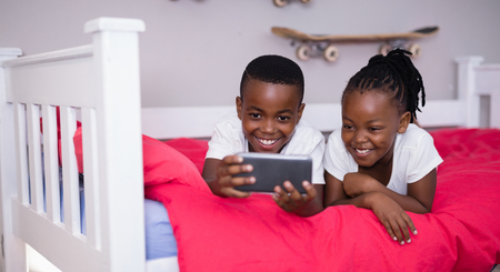 Happy siblings using mobile phone while lying on bed at home