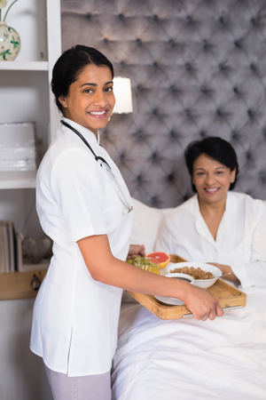 recuperation: Portrait of smiling nurse giving breakfast to patient resting on bed at home