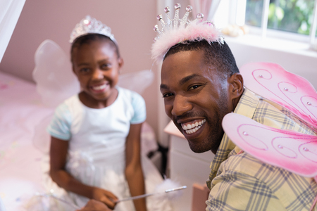 dressing up costume: Portrait of cheerful father and daughter wearing costume wings at home