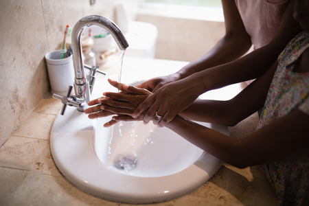 Mid section of mother and daughter washing hands at sink in bathroom Stock Photo