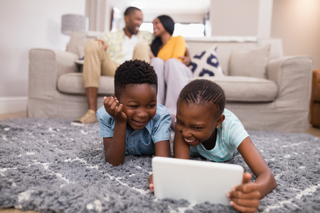 grey rug: Smiling children using digital tablet while parents siting on sofa at home Stock Photo