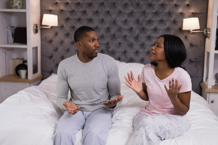 Young couple arguing in bedroom at home