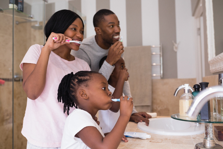 Happy parents with children brushing teeth in bathroom at home