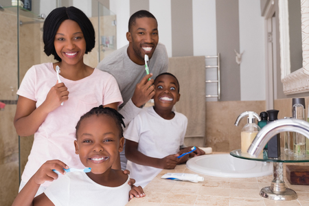 Portrait of happy family brushing teeth in bathroom at home Stock Photo