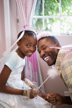 dressing up costume: Portrait of cheerful father and daughter holding wands while wearing costumes