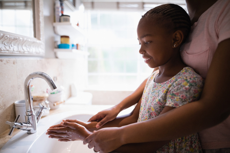 Mid section of mother assisting daughter while washing hands at bathroom sink
