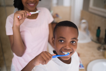 Portrait of boy with mother brushing teeth at home