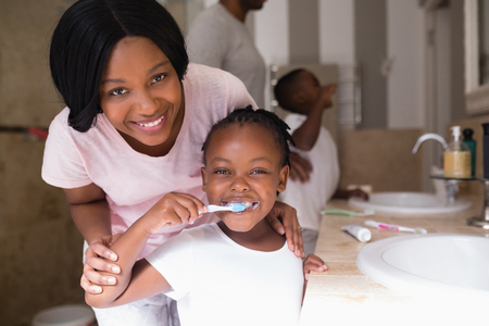 娘が自宅のバスルームで歯を磨くと笑顔の母の肖像 写真素材