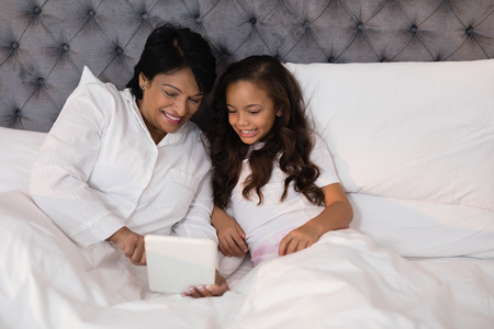 generation gap: High angle view of smiling grandmother and granddaughter using digital tablet on bed at home
