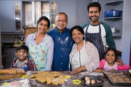 generation gap: Portrait of smiling multi-generation family standing together in kitchen at home Stock Photo