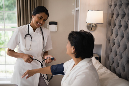 Smiling nurse checking blood pressure of patient resting on bed at home