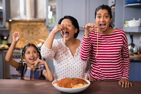 Happy multi-generation family eating spaghetti in kitchen at home