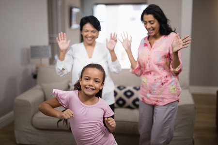 Portrait of smiling girl dancing with family at home