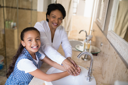 Portrait of grandmother and granddaughter washing hands at bathroom sink Stock Photo