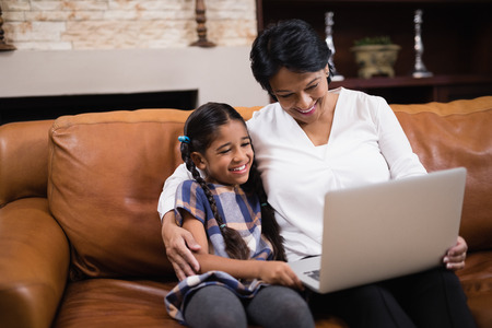 generation gap: Smiling woman with granddaughter using laptop while sitting on sofa at home
